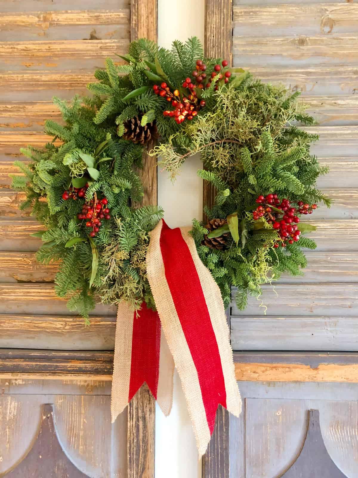 fresh christmas wreath on vintage shutters