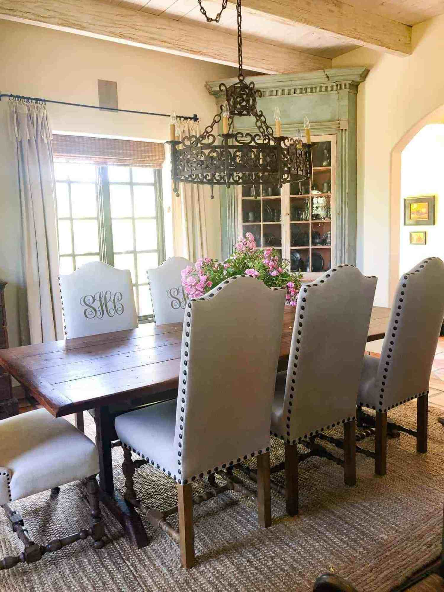 dining room with antiques and monogrammed chairs