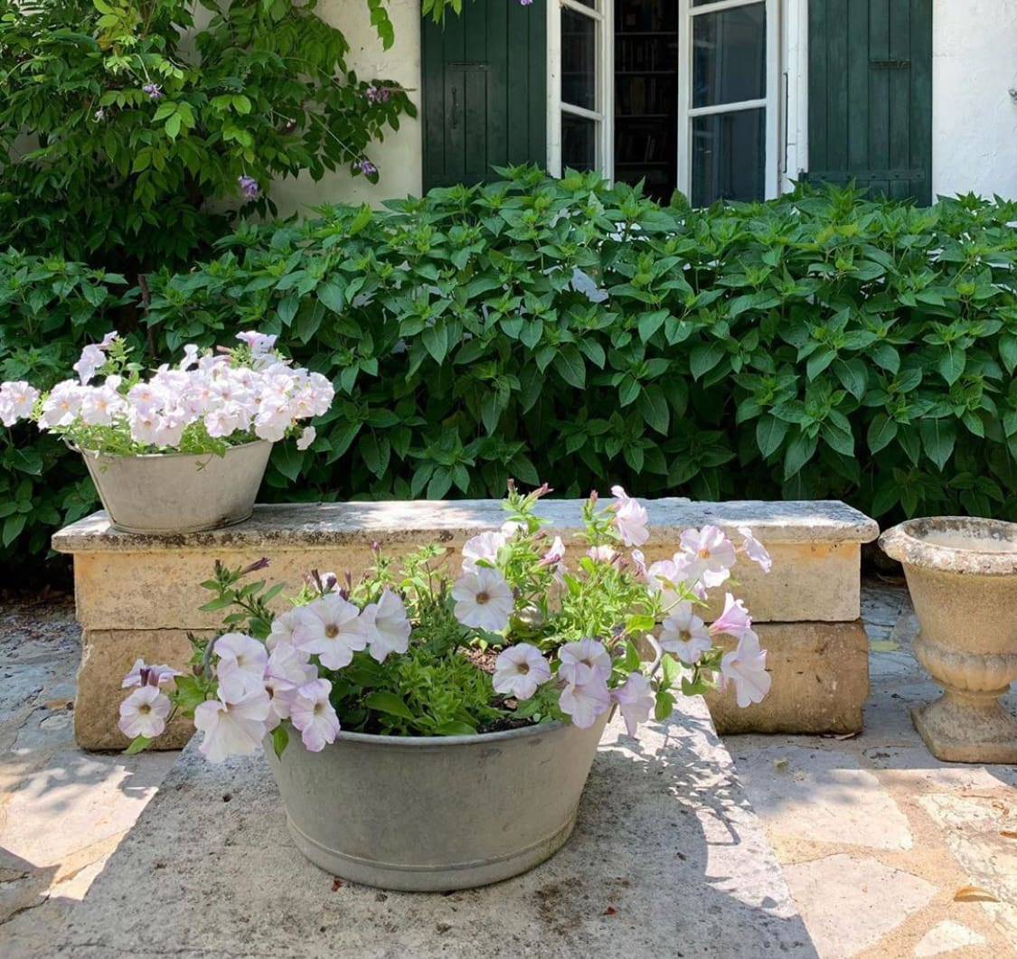 French garden with stone and galvanized pots